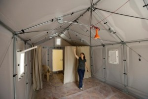 Roberta Russo, a communication officer for the UNHCR, shows a new a pre-fabricated house is to serve as an alternative to tents for refugees that designed by the Swedish furniture manufacturer IKEA for UNHCR, in Beirut, Lebanon, Wednesday July 24, 2013. A housing unit designed for the United Nations' refugee agency to offer shelter for those, fleeing conflict has become the latest source of friction between Lebanese politicians and aid organizations trying to manage the massive number of Syrian refugees in the country. Lebanon's refusal to set up any kind of organized accommodation for tens of thousands of Syrians, including refugee camps. (AP Photo/Hussein Malla)